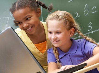 Portrait of two schoolgirls looking at the laptop during lesson