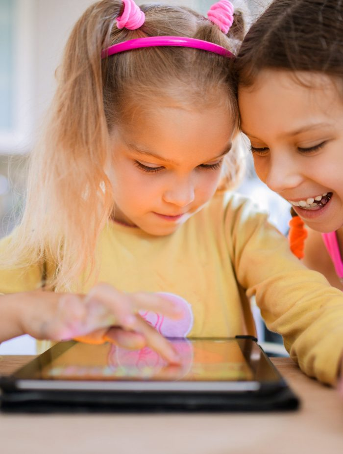 shutterstock-two 6 year old girls in front of an ipad